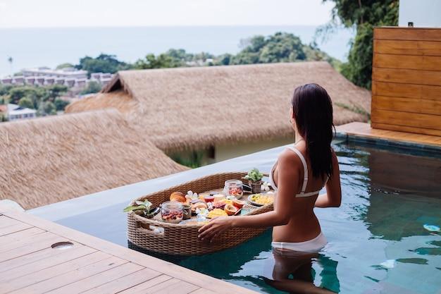 Femme ayant un petit-déjeuner tropical sain à la villa sur une table flottante