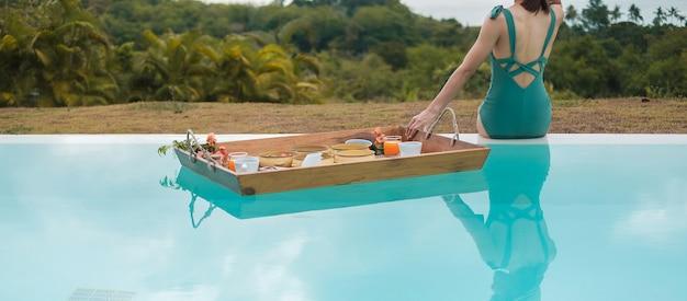 Femme ayant un plateau de petit-déjeuner flottant dans un hôtel de luxe avec piscine