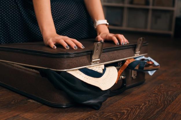 Femme ayant un problème avec la fermeture d'une valise. notion de voyage.