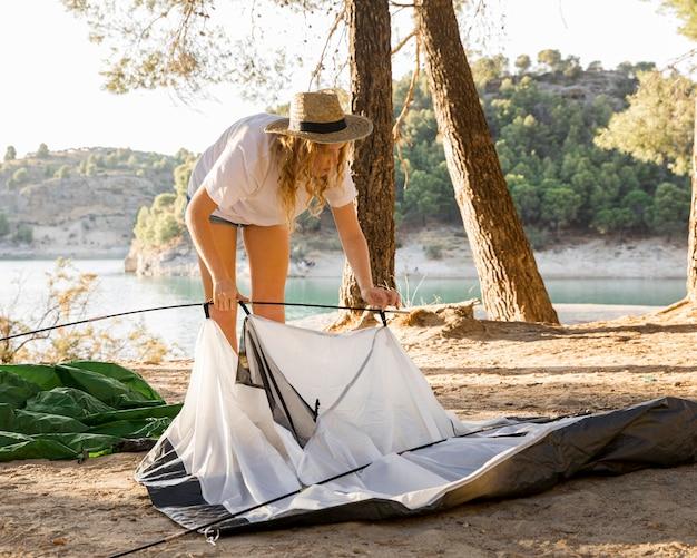 Femme ayant des problèmes avec la tente