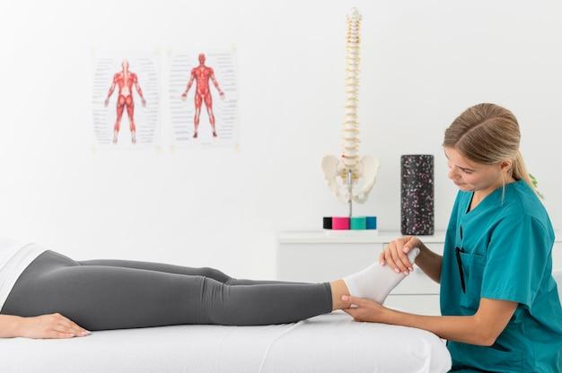 Femme ayant une séance de physiothérapie dans une clinique