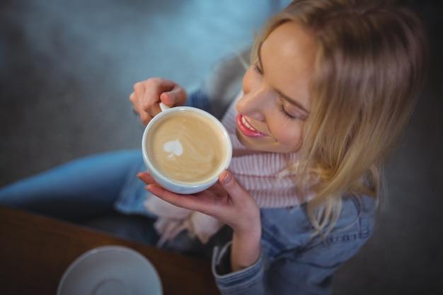 Femme ayant une tasse de café dans un café ©