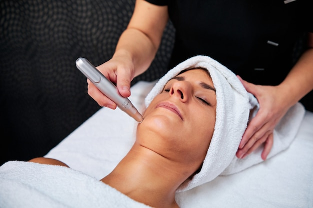 Femme ayant traitement microneedling dans spa
