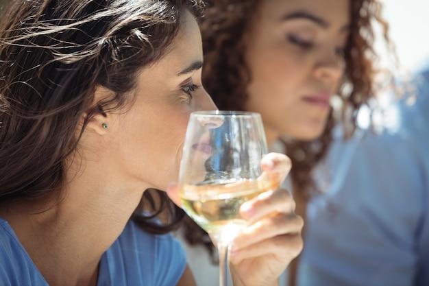 Femme ayant un verre de vin au restaurant