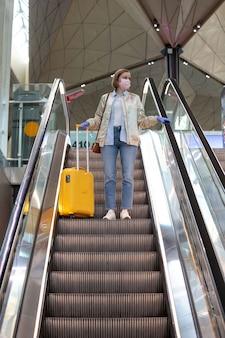 Femme avec des bagages jaunes se tient sur l'escalator au terminal de l'aéroport presque vide en raison de la pandémie de coronavirus