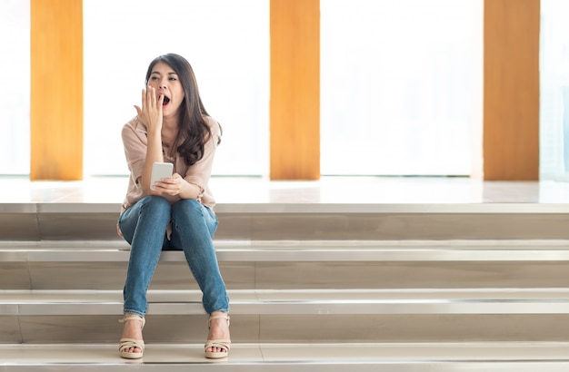 Femme bâillant en utilisant un smartphone
