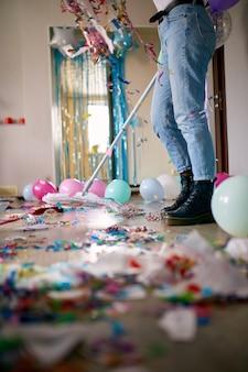 Femme avec balai de nettoyage désordre de plancher dans la chambre après confettis de fête