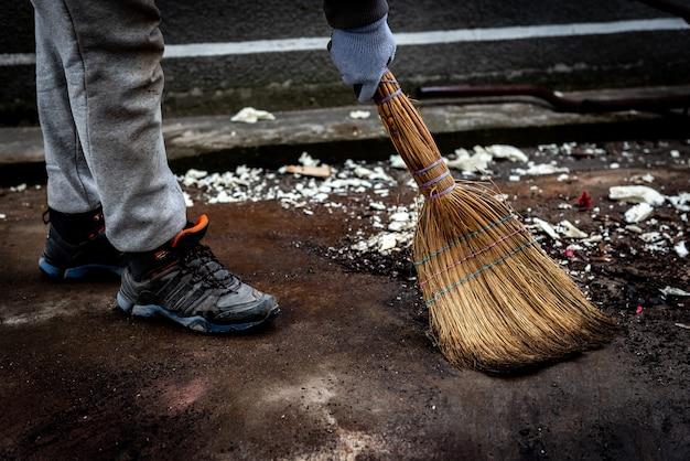 Une femme balaie la poubelle. nettoyer la zone des ordures dans la cour extérieure.