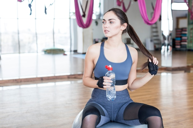 Femme sur la balle en forme avec de l'eau