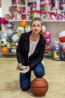 Femme avec ballon et dollars dans un magasin de jouets