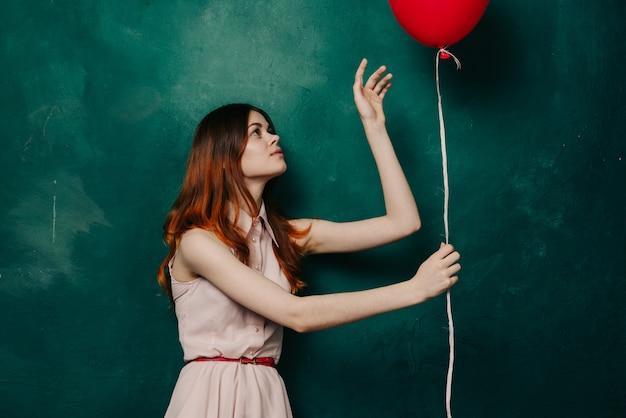 Femme avec des ballons dans ses mains dans une robe