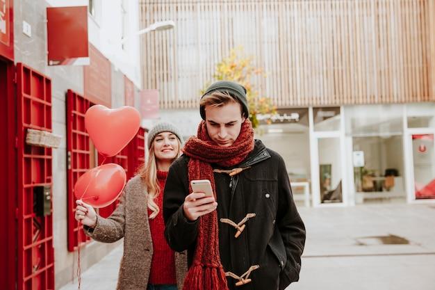 Femme avec des ballons venant à l'homme avec le téléphone