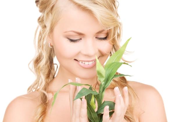 Femme avec bambou sur mur blanc