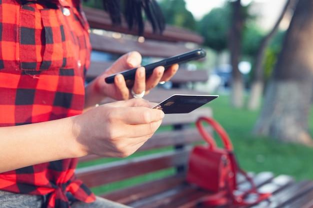 Une femme sur un banc tient un téléphone et une carte bancaire