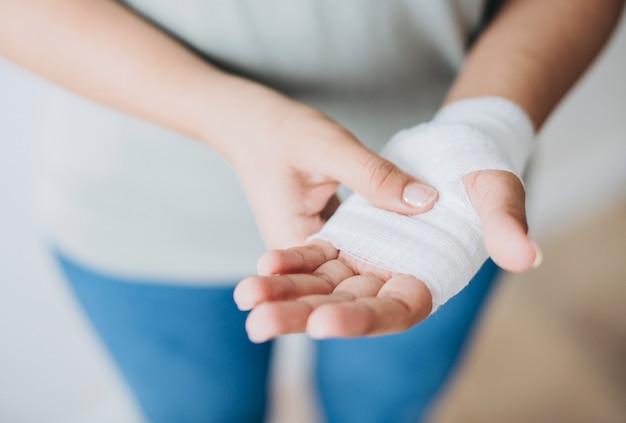 Femme avec un bandage de gaze enroulé autour de sa main