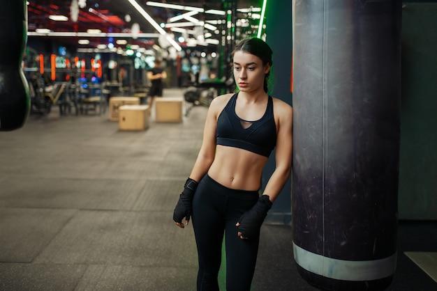 Femme en bandages de boxe noirs pose au sac de boxe, formation de boîte.