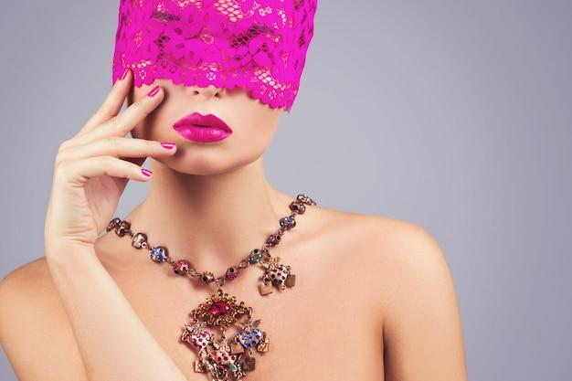 Femme avec un bandeau rose sur les yeux