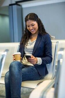 Femme de banlieue avec tasse de café à l'aide de téléphone mobile dans la zone d'attente