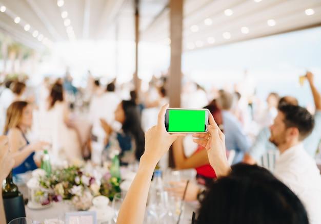 Femme à un banquet de mariage filmant une fête sur un smartphone en gros plan