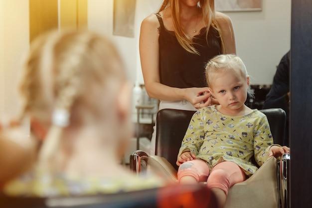 Une femme de barbier fait une jolie coiffure à la mode pour une jolie petite fille blonde dans un salon de coiffure moderne, un salon de coiffure. le coiffeur fait la coiffure pour le jeune bébé dans le salon de coiffure. concept coiffure et beauté