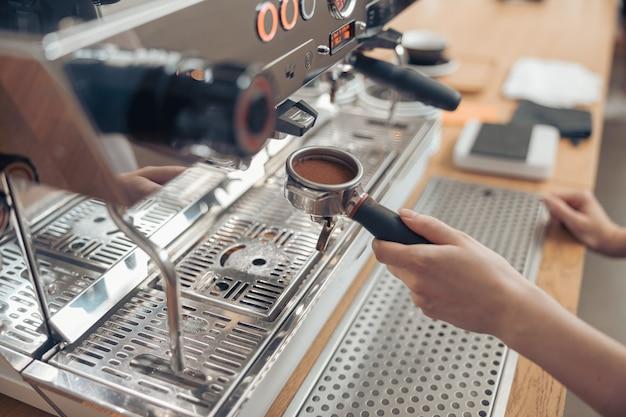 Femme barista à l'aide d'une machine à café moderne à la cafétéria
