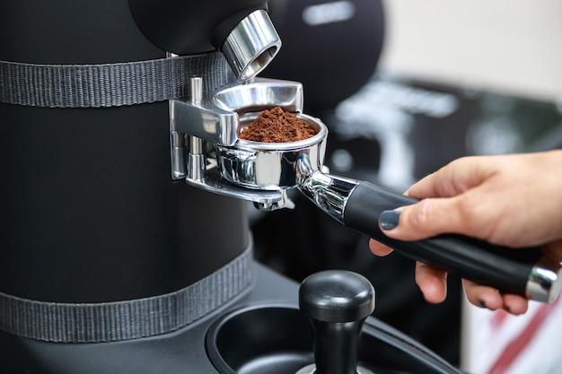 Femme barista broyer les grains de café dans le porte-filtre