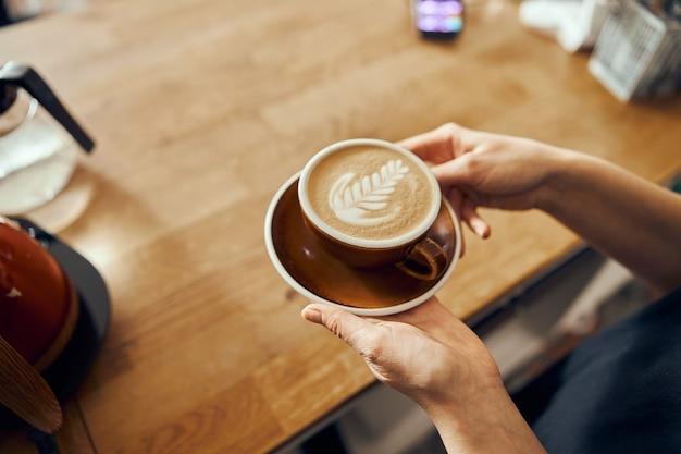 Femme barista donnant l'ordre au client au café branché. tasse à café avec art latte.