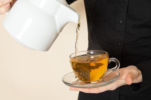 Femme barista en pantalon chemise noire avec des ingrédients de l'équipement de thé séché brun café faisant du thé sur le mur blanc
