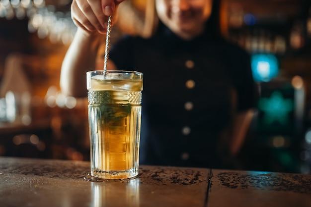 Femme barman remuer la boisson dans un verre