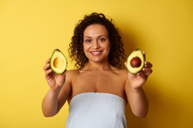 Une femme basanée aux cheveux bouclés, enveloppée dans une serviette de bain tenant les moitiés d'avocat et les montrant à la caméra, mignon souriant avec sourire à pleines dents tout en posant