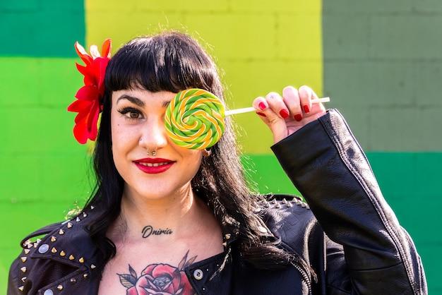 Femme à bascule tatouée en veste de cuir et fleur dans les cheveux sur un mur vert couvrant un œil avec une sucette géante.