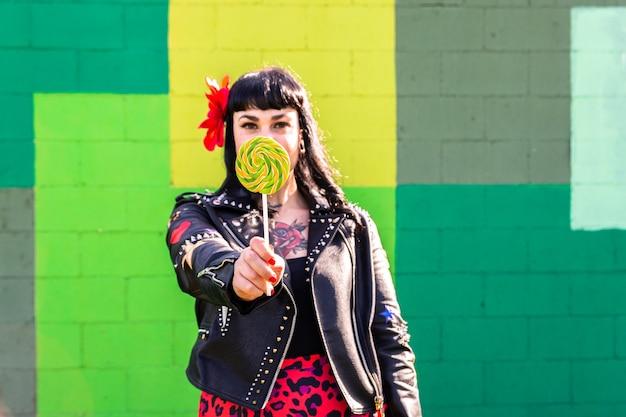 Femme à bascule tatouée en veste de cuir et fleur dans les cheveux sur un mur vert tenant une sucette géante.