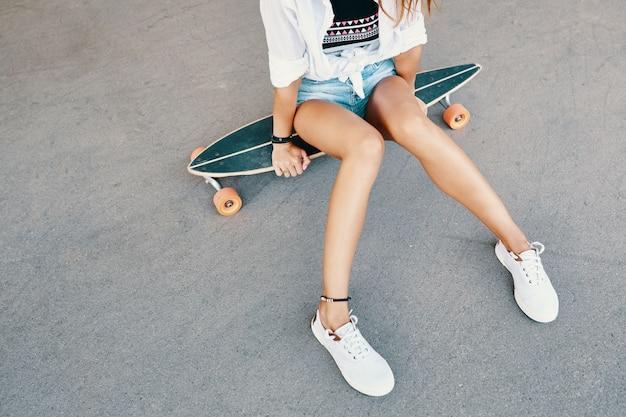 Femme en baskets équitation planche à roulettes en plein air sur la surface asphaltée.