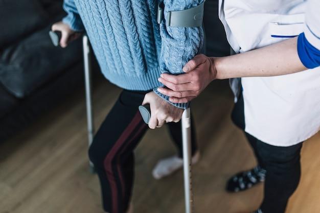 Femme avec des bâtons dans la maison de retraite