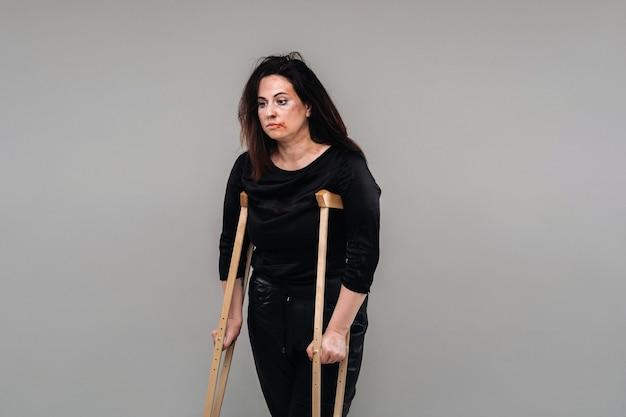 Une femme battue en vêtements noirs avec des béquilles dans les mains sur fond gris.