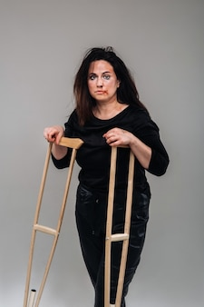 Une femme battue en vêtements noirs avec des roulettes dans ses mains sur un mur gris