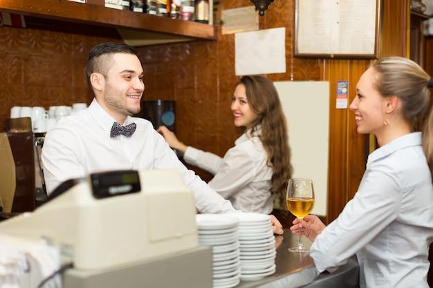 Femme bavardant avec les barmen