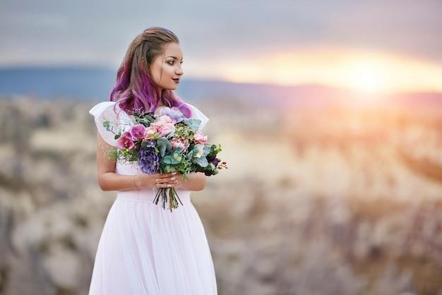 Une femme avec un beau bouquet de fleurs dans ses mains se dresse sur la montagne dans les rayons du coucher de soleil de l'aube. belle robe longue blanche sur le corps de la fille. mariée parfaite aux cheveux roses