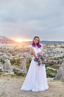 Femme avec un beau bouquet de fleurs dans ses mains se dresse sur la montagne dans les rayons du soleil couchant. belle robe longue blanche sur le corps de la femme. mariée parfaite aux cheveux roses