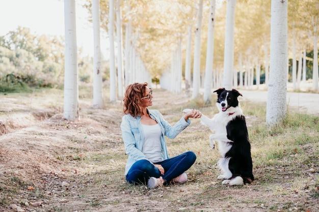 Femme et beau chien border collie assis dans un chemin d'arbres à l'extérieur.
