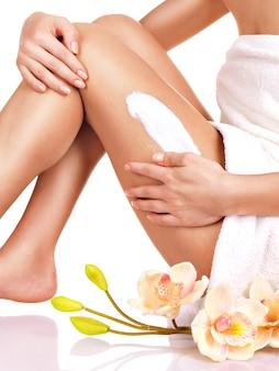 Femme avec un beau corps à l'aide d'une crème sur sa jambe sur un fond blanc