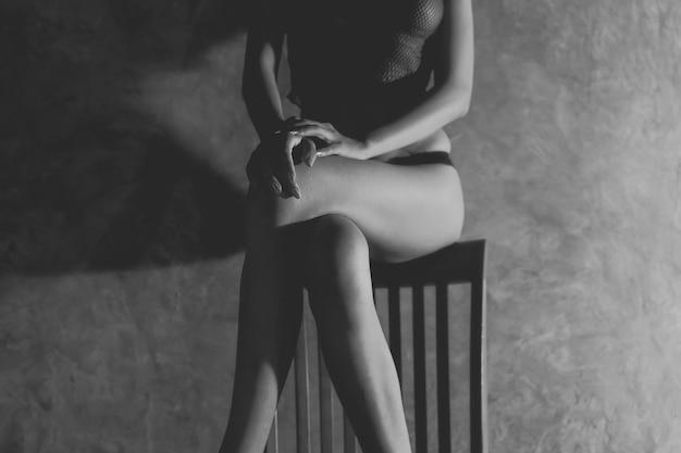 Femme avec un beau corps nu couvert de tissu blanc sur le lit.