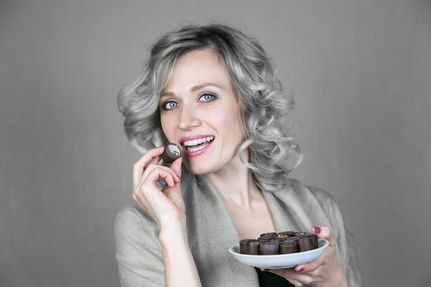 Une femme avec un beau sourire mange des bonbons.