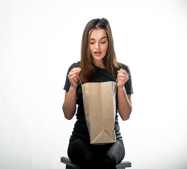 Une femme avec un beau sourire regarde le sac d'épicerie. fond isolé. fermer.