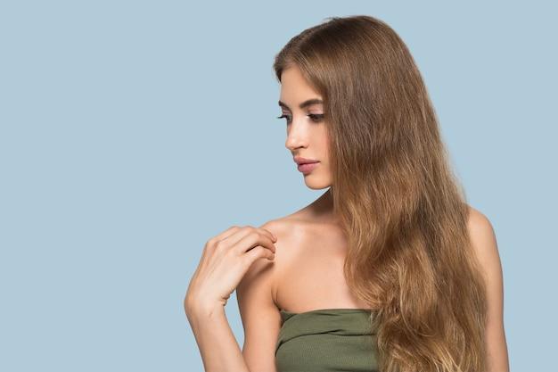 Femme beau visage en bonne santé. jeune mannequin de beauté se touchant. fond de couleur. bleu