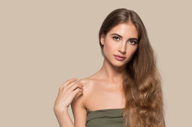 Femme beau visage en bonne santé. jeune mannequin de beauté se touchant. fond de couleur. brun