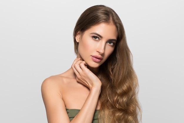 Femme beau visage en bonne santé. jeune mannequin de beauté se touchant. fond de couleur. gris