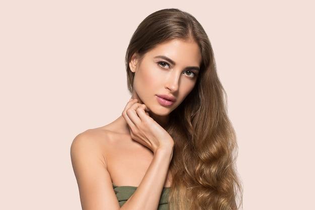 Femme beau visage en bonne santé. jeune mannequin de beauté se touchant. fond de couleur. rose
