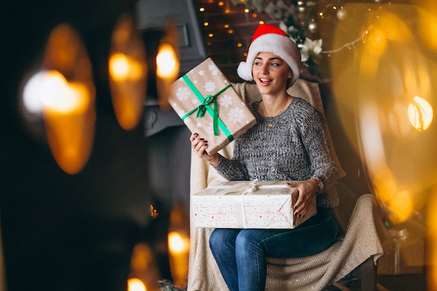Femme avec beaucoup de cadeaux par arbre de noël