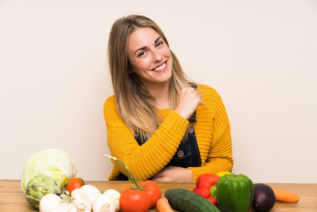 Femme avec beaucoup de légumes célébrant une victoire